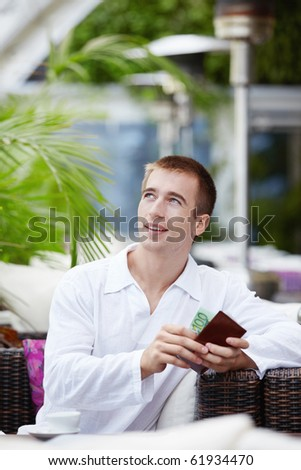 Man gets money from her purse at a restaurant - stock photo