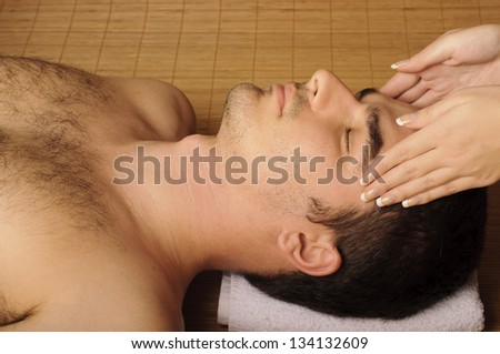 Man getting a face massage, at spa - stock photo