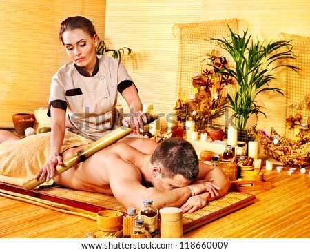 Man getting bamboo massage. Female therapist. - stock photo