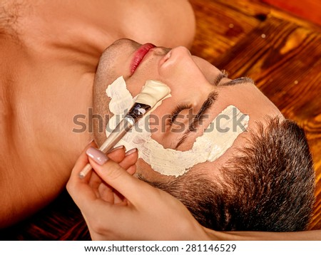 Man getting clay facial mask in beauty spa. - stock photo