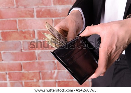 Man getting dollar banknotes out of purse on brick wall background