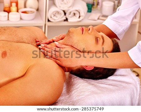 Man getting facial  and neck massage in beauty spa. - stock photo