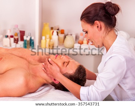Man getting facial  massage in beauty spa. Two people. - stock photo