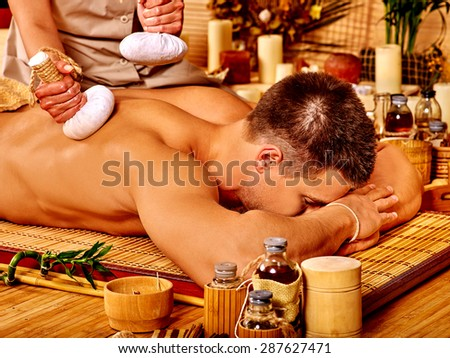 Man getting herbal ball massage treatments  in spa. - stock photo