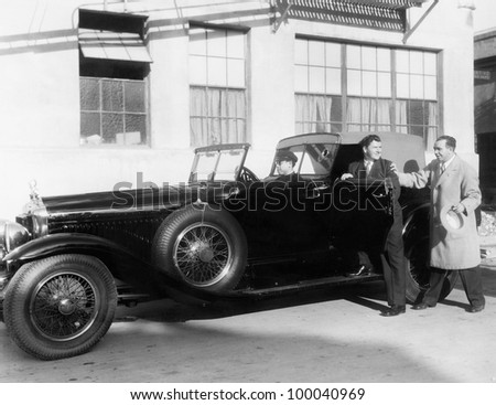 Man getting into car with chauffer - stock photo