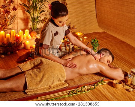 Man getting massage treatments  in spa with burning candles. - stock photo