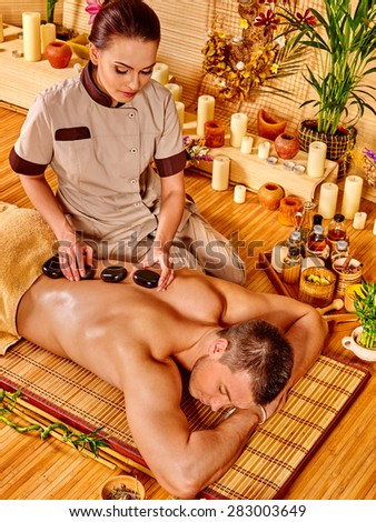 Man getting stone therapy massage in bamboo spa. - stock photo