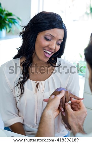 Man gifting finger to woman at home - stock photo
