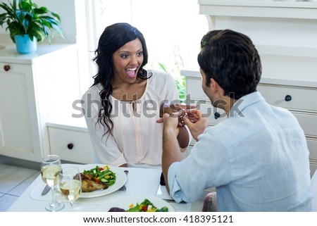 Man gifting finger to woman while having lunch in kitchen - stock photo