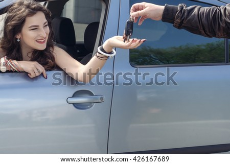 Man gives a girl the keys to the car. Girl sitting in car and smiling. Concept: purchase, transportation, car - stock photo