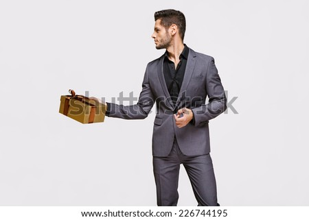 Man gives a present wrapped in gold gift paper, isolated on white - stock photo