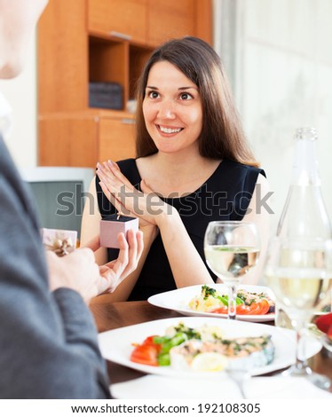 man gives a ring to his girlfriend during dinner - stock photo