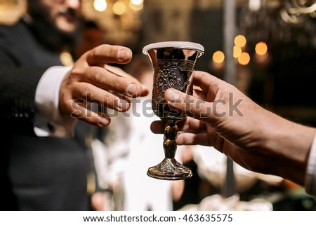 Man gives to another Jew a silver glass with drink