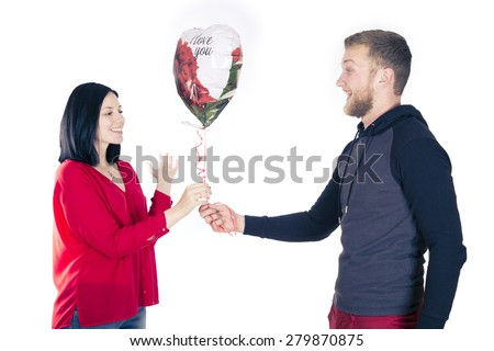 Man giving a balloon heart to a woman;