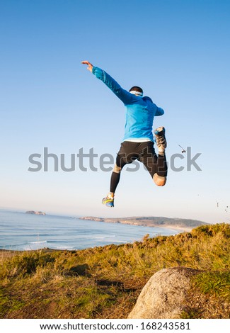 Man giving a big jump while practicing trail running with a coastal landscape in the background. - stock photo