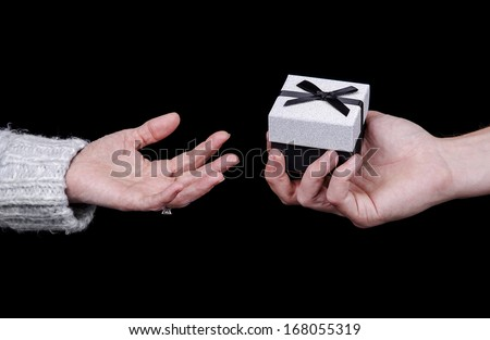 man giving a gift box to a woman on black background - stock photo