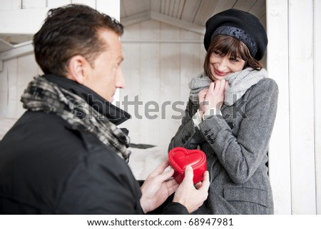 Man giving a heart shaped box to a beautiful woman, Valentine's Day, Anniversary or Birthday - stock photo