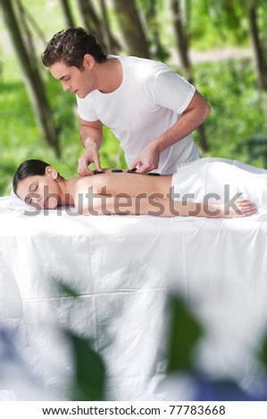 Man giving a hot mineral sacred stone treatment to a woman - stock photo