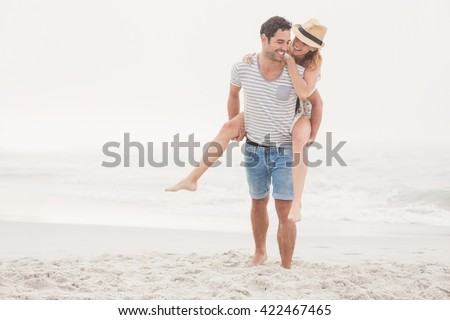 Man giving a piggy back to woman on the beach on a sunny day - stock photo