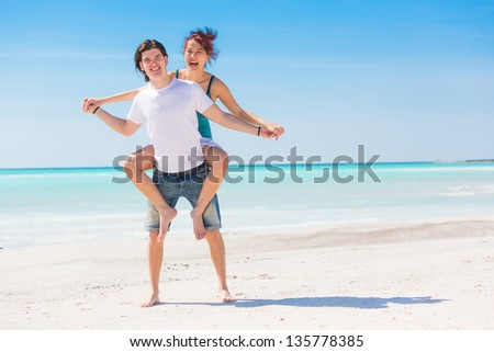 Man Giving a Piggyback Ride to His Girlfriend - stock photo