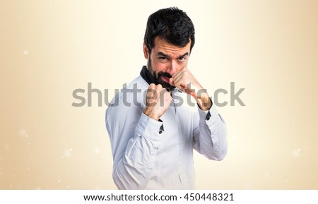 Man giving a punch over ocher background