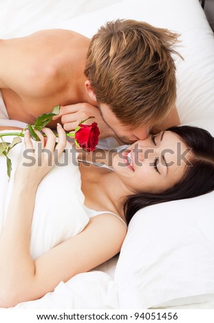 Man giving a rose and a kiss to his beautiful wife in bed, young lovely couple lying in a bed, happy smile love, girl with closed eyes, top above view