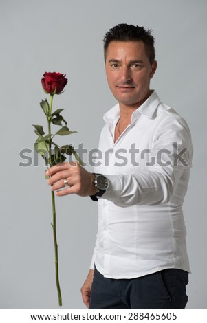 Man giving a rose isolated on grey background