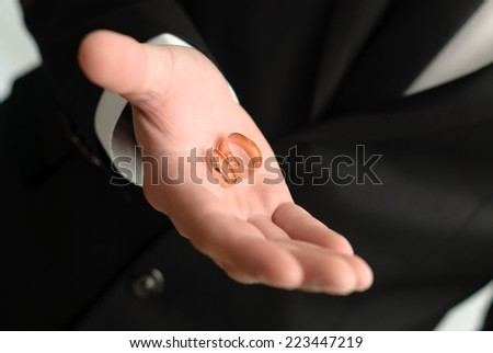 man giving a two wedding golden rings - stock photo