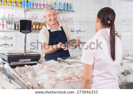 Man giving a white salmon to a costomer - stock photo