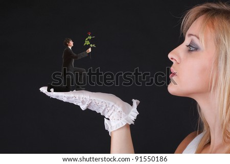 Man giving beautiful blonde woman a rose - white gloves black background - stock photo