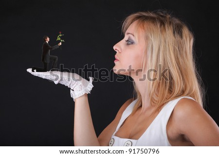 Man giving beautiful blonde woman a rose - white gloves black background