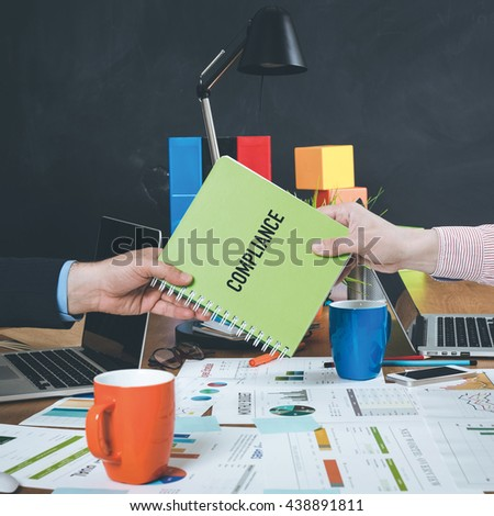 Man giving book which written Compliance - stock photo