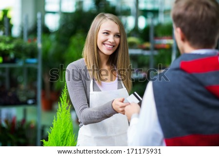 Man giving credit card to the saleswoman - stock photo