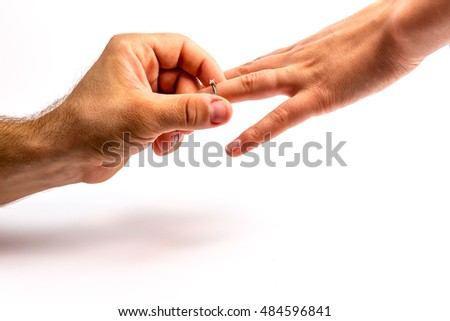 man giving engagement ring to his fiancee on white background