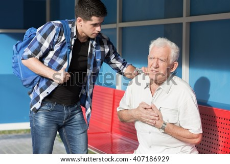 Man giving first aid to senior with heart attack - stock photo