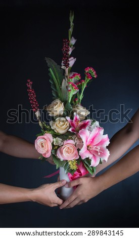 Man giving flowers to a man on dark background - stock photo