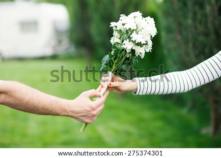 Man giving flowers to a woman - stock photo