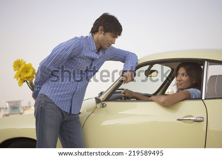 Man giving flowers to woman - stock photo