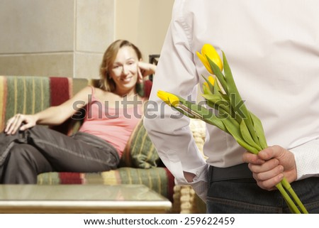 Man giving flowers to woman. Focus on the man  - stock photo