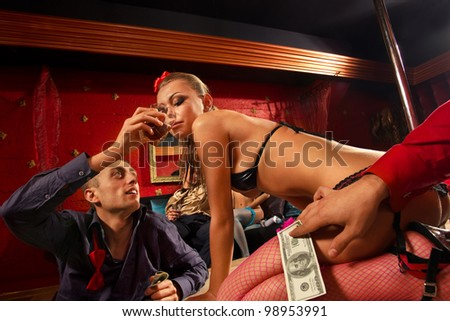 Man giving glass of whiskey to stripteaser woman on stage - stock photo