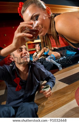 Man giving glass of whisky to stripteaser woman on stage - stock photo