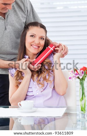 Man giving happy smiling woman a red birthday gift - stock photo