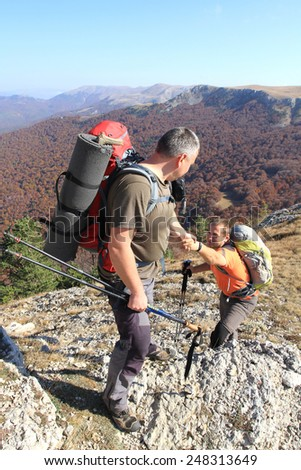 Man giving helping hand to friend to climb mountain rock cliff. - stock photo