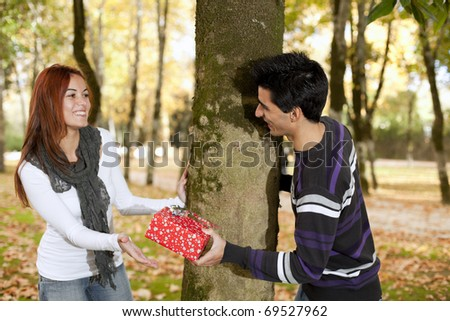 man giving her girlfriend a valentine day present (selective focus with shallow DOF) - stock photo