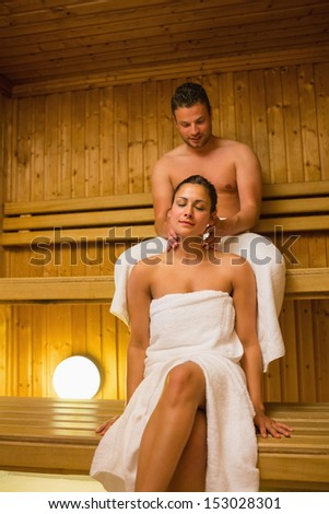 Man giving his girlfriend a neck massage in sauna wearing white towels and smiling - stock photo