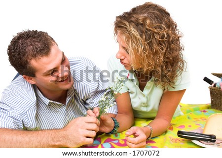 Man giving his girlfriend some fieldflowers during their summer picnic - stock photo