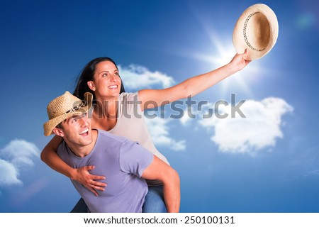 Man giving his pretty girlfriend a piggy back against bright blue sky with clouds - stock photo