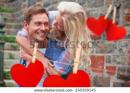 Man giving his pretty girlfriend a piggy back against hearts hanging on a line - stock photo