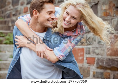Man giving his pretty girlfriend a piggy back on a sunny day in the city - stock photo