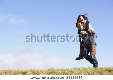 Man Giving His Wife A Piggy Back Ride In Park - stock photo